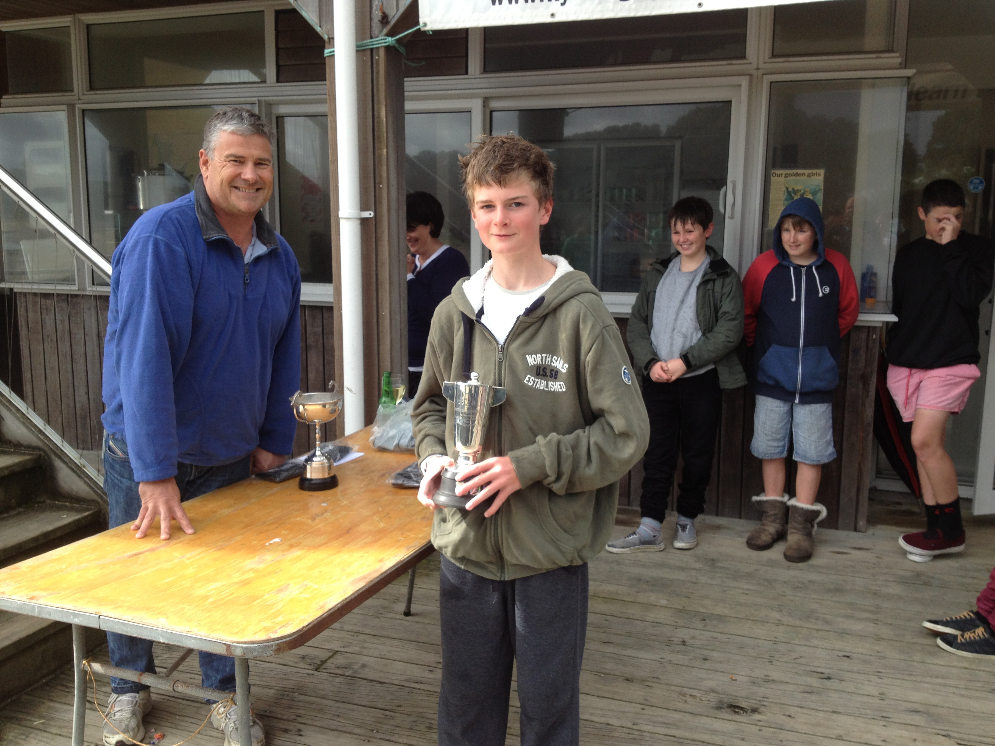 Henry Haslett receives his Auckland P Class Champ trophy from Jason Morgan Commodore KYC